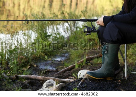 female fishing at a calm lake in the north of sweden - stock photo