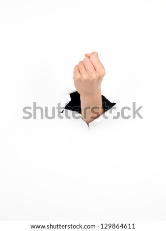 female fist through a hole in a white paper, tough gesture, isolated - stock photo