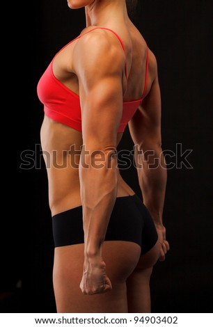 Female fitness bodybuilder posing against black background - stock photo