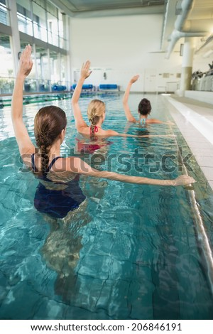 Female fitness class doing aqua aerobics in swimming pool at the leisure centre - stock photo