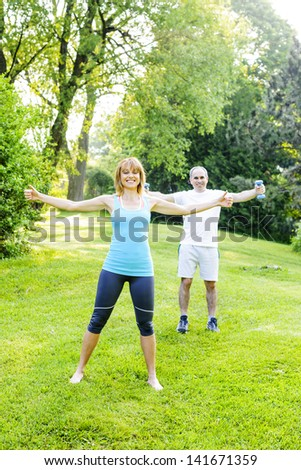 Female fitness instructor exercising with middle aged man outdoors in green park - stock photo