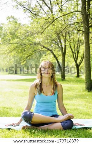 Female fitness instructor in lotus yoga pose outdoor at spring park - stock photo