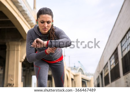 Female fitness jogger on a run adjusting her smart watch checking time and heart rate urban city - stock photo