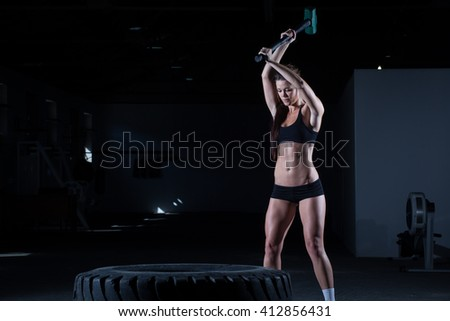 Female fitness model hitting a tractor tyre with hammer in a cross fit gym during intense training. - stock photo