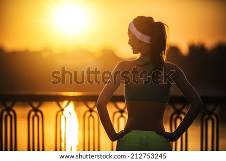 Female fitness model training outside in the city on a quay standing in a sunny bright light on sunrise. Sport lifestyle. - stock photo