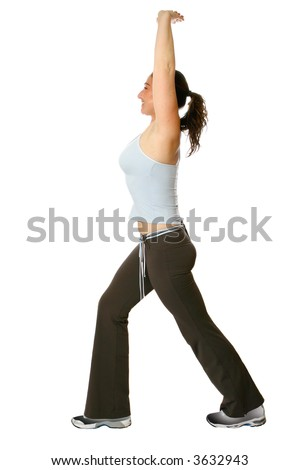 Female fitness trainer doing her back stretch, both arms up high above head, stretching the spine, lower back and along with the thigh muscle. - stock photo