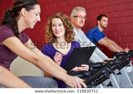Female fitness trainer helping woman on spinning bike in fitness center - stock photo