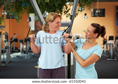 Female fitness trainer in gym talking to another woman - stock photo