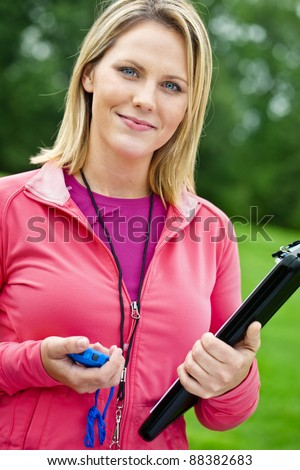 Female fitness trainer with stopwatch and clipboard - stock photo