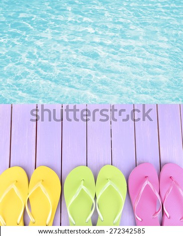 Female flip flops on wooden platform beside sea - stock photo