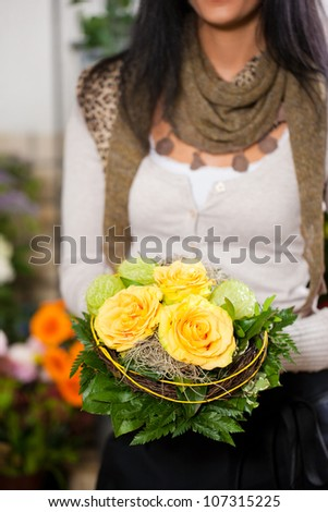 Female florist in flower shop or nursery presenting her plants on display - stock photo