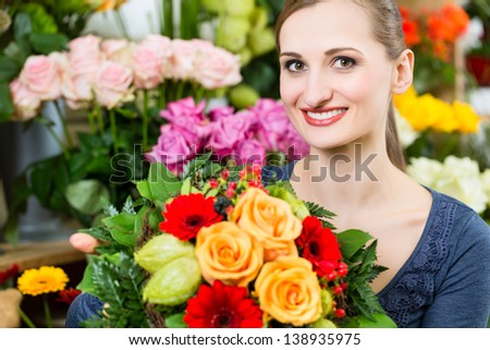 Female florist in flower shop or nursery presenting yellow roses - stock photo