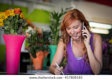Female florist taking order on mobile phone in the flower shop - stock photo