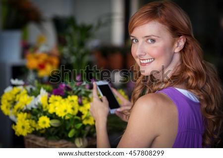 Female florist taking photogrpah of flower basket in the flower shop - stock photo