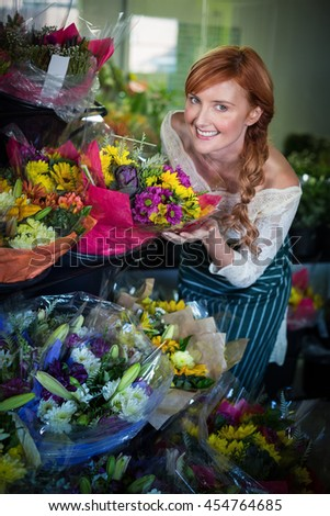Female florist touching flower bouquet in the flower shop - stock photo