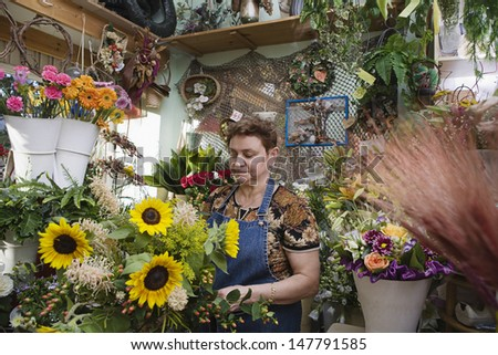 Female florist working in the shop - stock photo