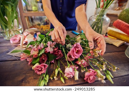 Female florist working with flowers in workshop - stock photo