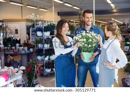 Female florists assisting male customer in buying flower plants at shop - stock photo