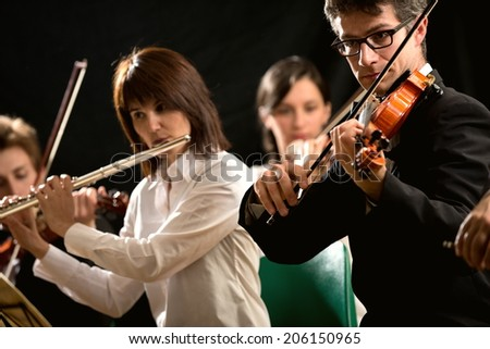 Female flutist and violinist performing in classical music concert. - stock photo