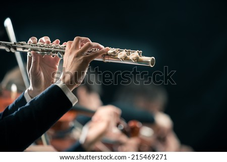 Female flutist close-up with orchestra performing on background.