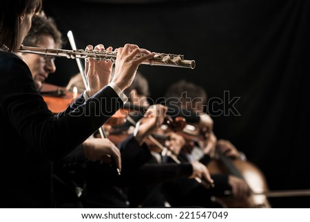 Female flutist close-up with orchestra performing on background. - stock photo