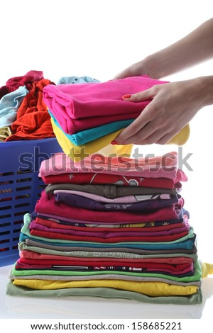 Female folding children's clothes on isolated background - stock photo