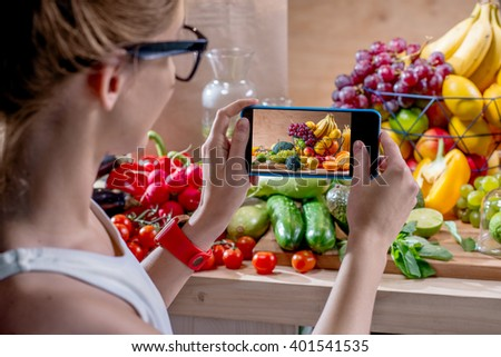 Female food photographer photographing with smartphone fresh fruits and vegetables