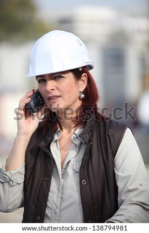 Female foreman using radio to communicate - stock photo