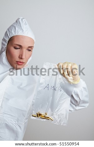 Female forensic scientist holding ammunition as evidence - stock photo