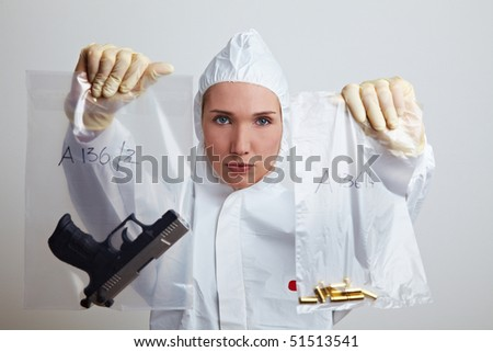 Female forensic scientist holding weapon and ammunition