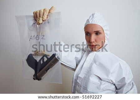 Female forensic scientist holding weapon and ammunition - stock photo