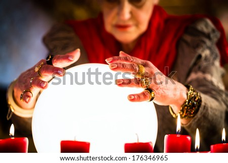 Female Fortuneteller or esoteric Oracle, sees in the future by looking into their crystal ball during a Seance to interpret them and to answer questions - stock photo