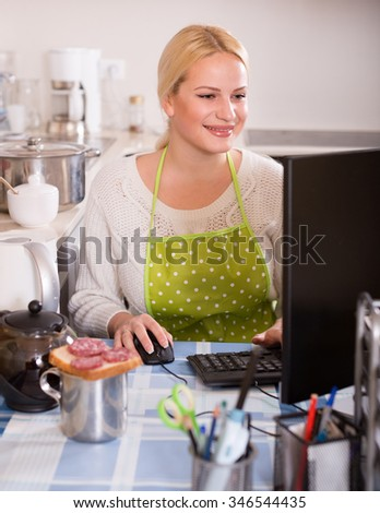 Female freelancer  in apron with PC, tea and sandwich at kitchen table