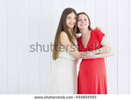 Female friend with pregnant woman on white background
