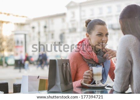 Female friends at sidewalk cafe - stock photo