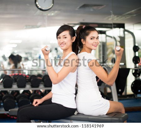 Female friends being happy with training together back to back - stock photo