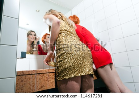 Female friends checking their make up at the toilet of a club or at a party - stock photo