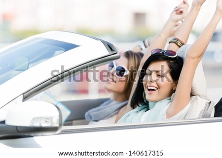 Female friends driving car with the hands up and having fun on the vacation - stock photo