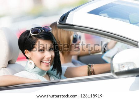 Female friends driving white car and having fun on the vacation