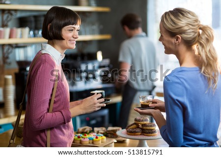 Female friends interacting while having a cup of coffee in café