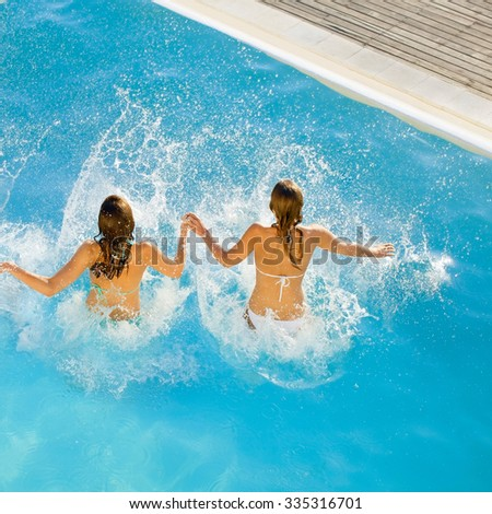 female friends jumping in pool at resort - stock photo