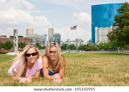 Female friends lying on the grass against the Indianapolis skyline - stock photo