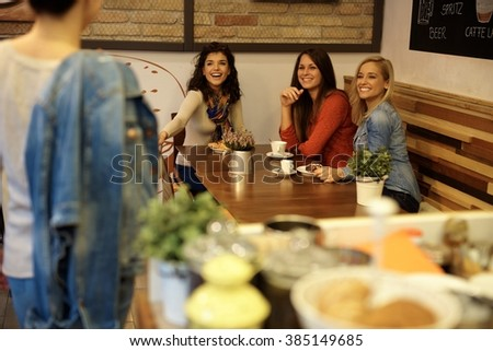 Female friends meeting in cafeteria, having fun. - stock photo