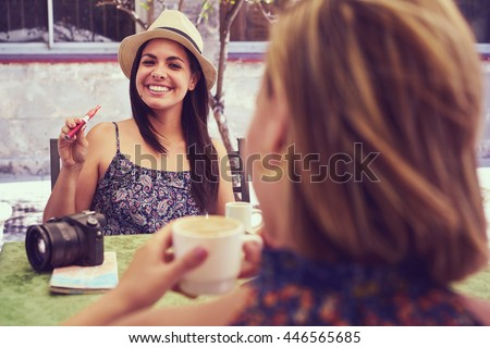 Female friends on holidays, young happy women sitting at bar smoking electronic cigarette.  - stock photo