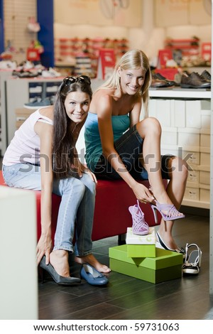 Female friends purchasing shoes - stock photo