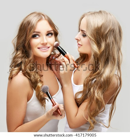 Female friends putting makeup