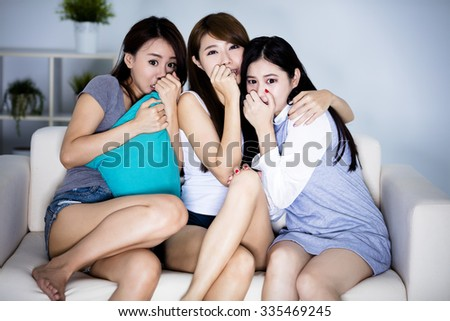 Female friends sitting on sofa and watching horror movie  - stock photo