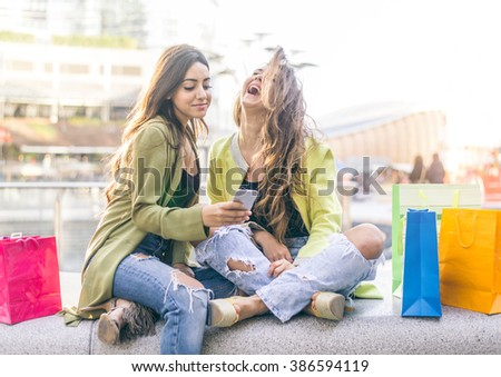 Female friends watching something funny on a smartphone - Girlfriends laughing and having fun outdoors - stock photo