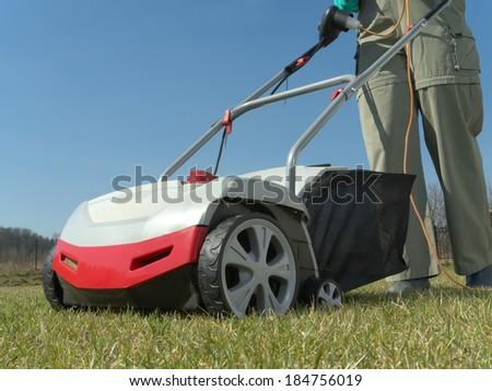 Female gardener scarifying her backyard lawn using electric scarifier - stock photo