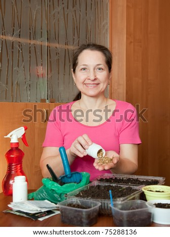 Female gardener sows seedlings at her  home - stock photo